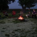 Salina -- Twilight dinner around the fire, visiting with extended family representing three generations of farmers.  The meal featured home grown beef, tomatoes, cantaloupe, plus dessert of  marshmallows heated over open flames to make smores.  Stories of the house where today's elders grew up, and the multiple barns nearby eventually knocked down by storms.  (Salina, Iowa) 20180810