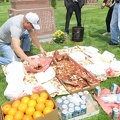 Pine Hills Cemetery -- Selecting small pieces of meat to offer to relatives in the afterlife.  Annual cemetery visit to remember clan members no longer with us, and ancestors in our lineage.  (Pine Hills Cemetery, Birchmount Road, Scarborough, Ontario) 20180520