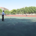 Wuhan U. of Technology -- Man exercising with diabolo spinning with string between two batons, on the exercise field in the middle of campus on a warm spring morning.  The short cut across the track has been closed off since our last visit, it's a long walk from the east gate to the College of Art and Design.  (Wuhan University of Technology, Wuhan, PR China) 20180419