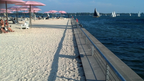 Sugar Beach umbrellas and sailboats in Toronto Harbour