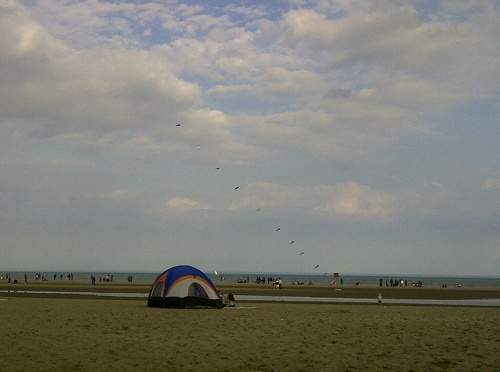 A string of kites, and a snall tent on the sand at Woodbine Beach