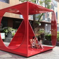 "Xintiandi Style -- Children attracted to #PenzoCAO (2019) ""Time Traveller"" at #XintiandiDesignFestival, sitting in bamboo chairs inside red crystal-like walls.  The circular part is hinged, and rotates.  Installation is one of many in the courtyard of a high-end fashion mall, shoppers are complemented by foreign tour groups crowding in the restaurants to the north.  (Xintiandi Style, Madang Road, Xintiandi, Shanghai, PR China) 20190317"