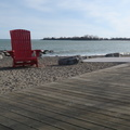 Woodbine Beach -- Big red chair is double-sized, not so functional for relaxing when facing away from the bay.  Bright, sunny day attracts pedestrians onto the boardwalk, but it's still cold enough to wear full-finger gloves on the bicycle.  (Woodbine Beach, Toronto, Ontario) 20190413