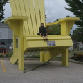 Sawdust City Brewing Co. -- Dull fall day to be sitting in the oversized Muskoka Chair, summer in cottage country has passed.  Climbing the structure has been made easier with safety ridges for traction, but it still takes nerve to dangle legs over the front.  The shape is different than an Adirondack Chair, the back is rounder and the arms are wider.  (Sawdust City Brewing Co., Muskoka Road N., Gravenhurst, Ontario) 20190914