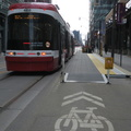 King Street West at Peter Street -- Encountered the first raised transit stop platform in town, where bicyclists and pedestrians take turns through a narrow lane previously a parking space.  On Easter Sunday, streetcars paused only momentarily, with few passengers boarding.  Only pedestrians of note were lined up outside the pharmacy, with respectable distances between them.  (King Street West at Peter Street, Toronto, Ontario) 20200412