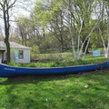 Tollkeepers Park -- Canoe unexpectedly found in park in Humewood neighbourhood, part of the #Butterflyway @DavidSuzukiFDN project installed in 2017, natural habitats for bees and butterflies.  Park has cottage from the 1850s, in use when roads had tolls for travellers on horseback or on wagons.  Grass is following the unkempt trend, as city services are limited during social isolation.  (Tollkeeper's Park, Bathurst Street at Davenport Road, Toronto, Ontario) 20200505