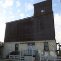 The Silver Mill -- Strangely shaped 3-storey former wooden-crib grain elevator from 1906, beside a former flour/grist mill on dead end road just north of railway tracks in east end of the city.  Building was used as a transdisciplinary arts centre, with municipal art organization vacating the premises in 2018.  Signage now minimized, redevelopment into a new high rise complex that will connect to the Danforth Go Train terminal was in council in 2019.  (The Silver Mill, 10 Dawes Road, East York, Toronto, Ontario) 20200512