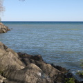 Ashbridges Bay East Breakwater -- Rocky berm shore onto Lake Ontario put in place to control sediment from the west, maintained by regional conservation authority.  The park is on lands historically a marsh.  Saw a couple lounging by the point, amongst the many cyclists and pedestrians enjoying spring temperatures.  Still too cool for beachwear, with strong winds from the east.  (Ashbridges Bay East Breakwater, Lakeshore Boulevard East, Toronto, Ontario) 20200520