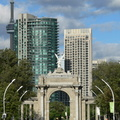 Princes Gates -- Rear view, looking eastward toward the city centre, of the Goddess of Winged Victory, with a single maple leaf in her hand.  The last two weeks of August normally see this street busy with the Canadian National Exhibition, but the pandemic led to cancellation.  Statue commemorated in 1972 was poured concrete, replaced by in 1987 by a polymer copy.  Nine pillars represent the nine provinces at that time.  (Princes Gates, Princes Boulevard, Toronto, Ontario) 20200829