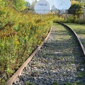 Unwin Avenue -- Industrial age rail leading to space age satellites?  Tracks rarely used from Toronto Container Port to the southwest, curve north beyond fence parallel to Leslie Street, then westbound alongside Lakeshore Boulevard as Keating Yard.  Earth stations that upload and download broadcast television video, and Internet to rural and remote areas on land leased from the city, will be moved to another Ontario location before year's end.  (Unwin Avenue, Toronto Portlands, Ontario) 20200928
