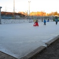 Harry Gairey Rink -- Parents giving children a feel of the ice with skate helper training aids, an improvement over pushing a chair around.  Slower movement on the pleasure pad to the south, faster circuits on the hockey pad to the north.  Artificial ice solidified with temperatures below freezing overnight, streets otherwise clear of snow.  (Harry Gairey Rink, Alexandra Park, Bathurst Street, Toronto, Ontario) 20201205