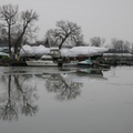 Ashbridges Bay -- At the perimeter near the shore, patches of films of ice beginning to form in the shallows.  Most boat owners seem to prefer covering their watercrafts with white, so dusk is almost monochromatic.  Towards the park, parents walking with their children bundled up in snowsuits.  (Ashbridges Bay, Lake Shore Boulevard East, Toronto, Ontario) 20201220