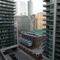 One City Hall -- View southeast from 12th floor of apartment tower in historic Old Chinatown.  After Asian businesses moved west to Spadina, a 12-storey office tower was built in 1974, then bombed by the Italian Mafia in 1977 and feared with bad feng shui.  In 1999 that tower was imploded, and then replaced by three towers completed in 2007.  (111 Elizabeth Street, Toronto, Ontario) 20210306