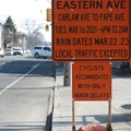 "Eastern Avenue at Carlaw Avenue -- Sign of the times with ""Cyclists Accommodated With Only Minor Delays"", suggesting that automobiles and trucks will be completed diverted.  Consistent with the joke that Canada has two seasons:  winter, and construction.  Temperature swing of 10 degrees Celsius has citizens abandoning parkas.  (Eastern Avenue at Carlaw Avenue, Riverside neighbourhood, Toronto, Ontario) 20210310"