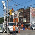 Queen Street East at Logan Avenue -- Overhead wires have been at this city intersection since the 1880s, presumable replaced many times over.  Second truck parked across the street was detaching cables, the poles further east have neater braids.  This tough urban streetscape might be improved by burying underground, but one block south used to be a marsh, suggesting geological as well as economic practicalities.  (Queen Street East at Logan Avenue, Riverside neighbourhood, Toronto, Ontario) 20210628