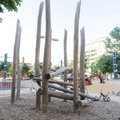 Lisgar Park -- Sculptural playground climber of logs may be better than artificial materials, planned as a safe place for toddlers.  In the plaza beyond, trees sparsely ring the open space, yet it seems unlikely that children would attempt ascending.  Park is a former 1900s warehouse site, constructed between 2014-2016, with the rise of apartments in the district.  (Lisgar Park, Abell Street, Toronto, Ontario) 20210723